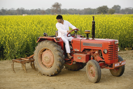 A farmer on his tractor Stock Photo - 80310526