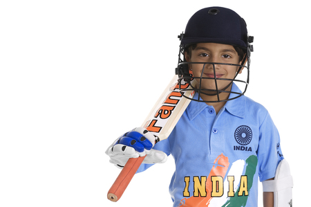 A boy in a cricketers outfit Imagens