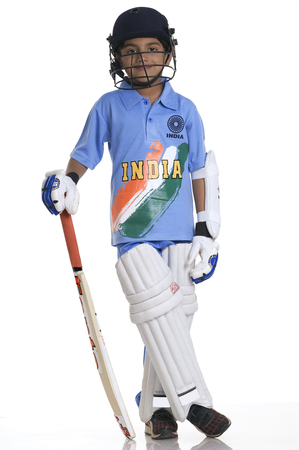 A boy in a cricketers outfit Stock Photo
