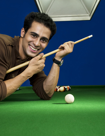 Man with cue stick Stock Photo