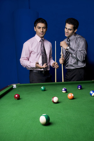 Colleagues playing pool Stock Photo