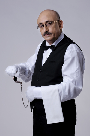 Butler with a pocket watch Stock Photo