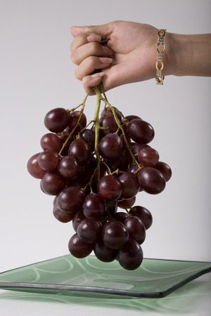 Holding grapes Stock Photo