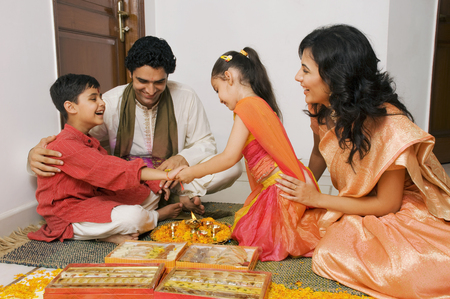Girl tying a rakhi Stock Photo