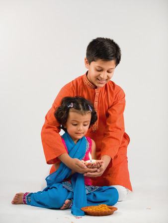 Boy and girl holding a diya together Stock Photo