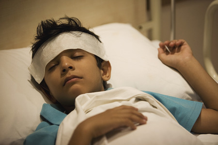 Boy sleeping with a damp cloth on his forehead Stock Photo