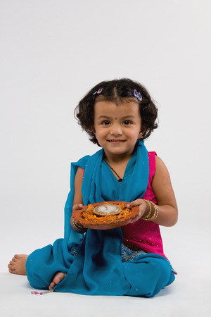 Girl holding a decorated diya Stock Photo