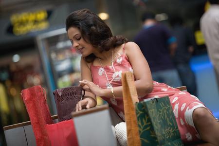 splurge: Woman admiring her shopping