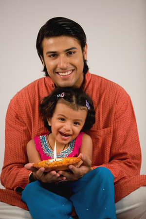 customs and celebrations: Girl holding a diya with her father