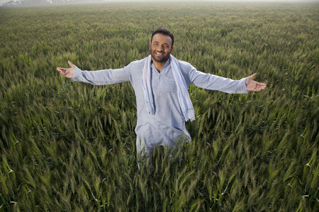 Portrait of an Indian man standing with arms out in a field