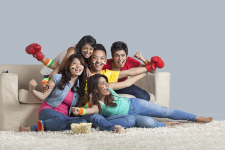 Portrait of cheerful young friends watching a boxing match together at home