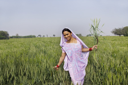 Portrait of an Indian female farm worker gliding through wheat field