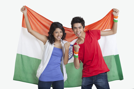 Portrait of happy young friends cheering while holding Indian flag over white background Stock Photo