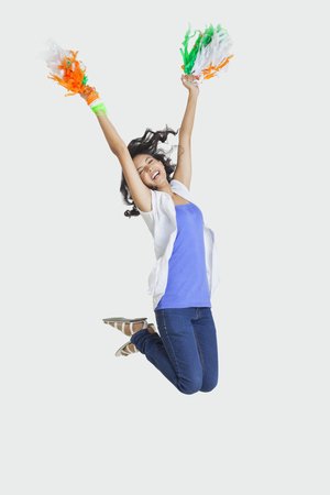 Full length of young female jumping in mid-air with Indian tricolor pom poms over white background Stock Photo