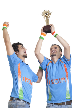 Young male friends in jerseys cheering up with winning trophy over white background