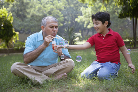 cross legged: Grandfather blowing bubbles for grandson Stock Photo