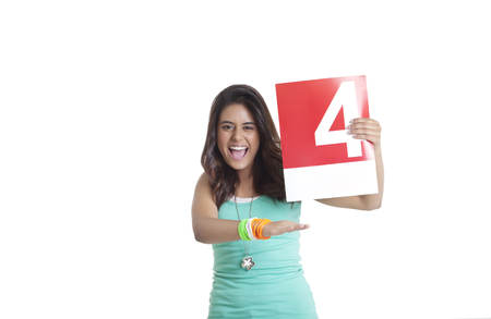 Portrait of an excited young woman holding a signaling a four over white background