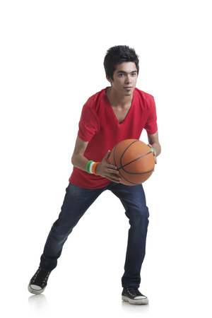 only one teenage boy: Full length of young boy ready to throw basketball over white background Stock Photo