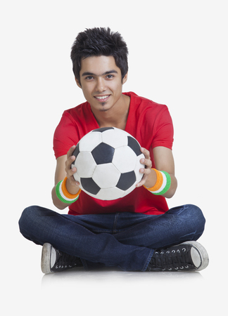 Portrait of young boy smiling while holding soccer ball over white background Stock Photo