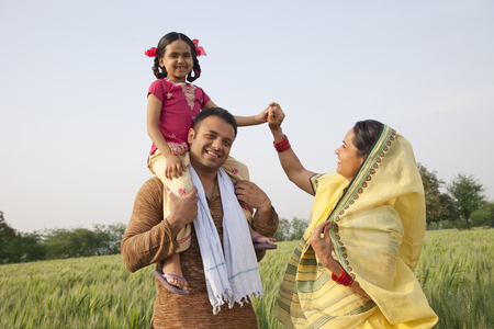 Family in field with girl on fathers shoulders