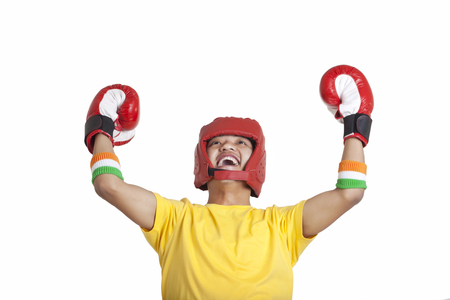 only one teenage boy: Cheerful young male boxer looking up with hands raised over white background Stock Photo
