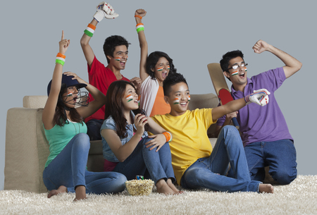 Happy young friends having a great time together while watching cricket match at home Stock Photo