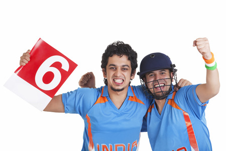 Portrait of cheerful male cricket fans in jerseys standing together over white background
