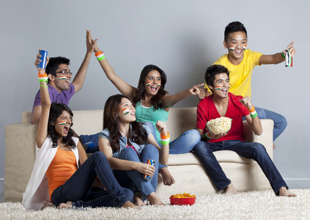 Excited young friends having great time together at home Stock Photo