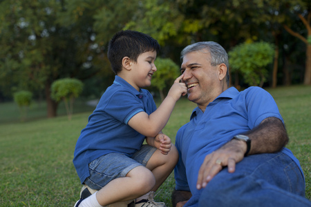 touching noses: Grandson touching his grandfathers nose Stock Photo