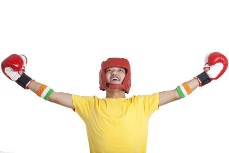 Happy young male boxer looking up with arms out over white background Stock Photo