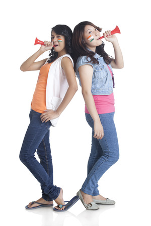 Full length portrait of young women in casuals with face painted holding vuvuzela over white background