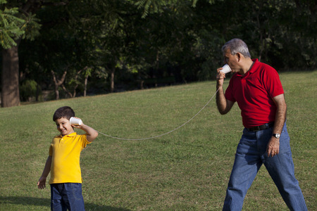 granddad: Grandfather and grandson talking through paper cups