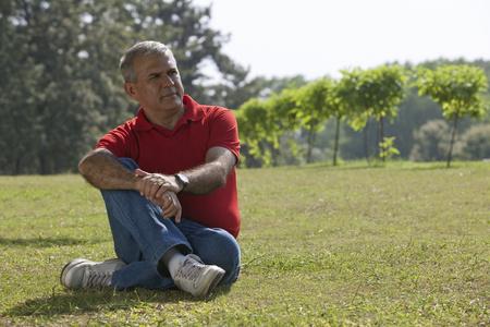 cross: Senior man sitting in a park
