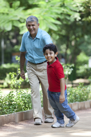 granddad: Grandfather and grandson taking a walk in a park Stock Photo