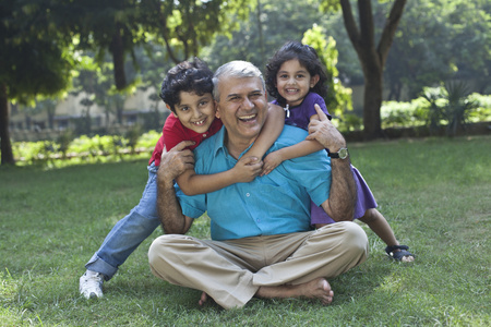 cross: Portrait of grandchildren hugging grandfather Stock Photo