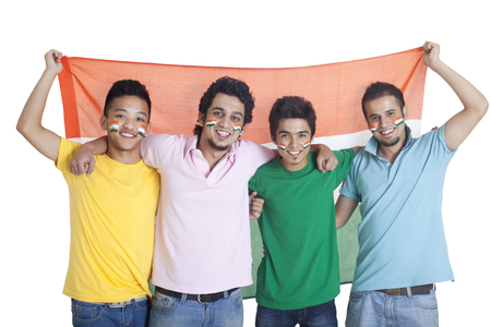 Portrait of happy young male friends standing together with Indian flag over white background