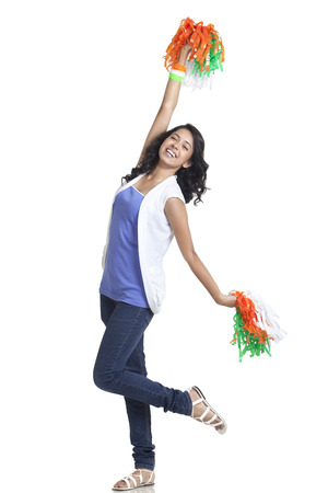 Full length of happy young woman cheering with Indian tricolor pom poms over white background