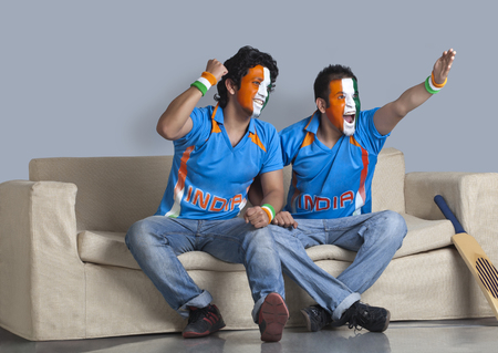 Excited male friends with face painted in Indian tricolor sitting together on sofa