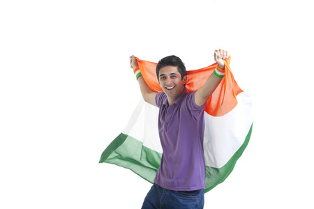 Portrait of happy young man in casual wear holding Indian flag over white background Stock Photo