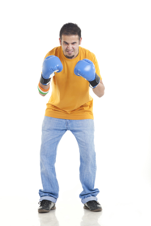 readiness: Full length portrait of aggressive young male boxer standing over white background Stock Photo