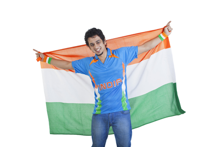 Portrait of young man in Indian cricket team jersey holding national flag over white background