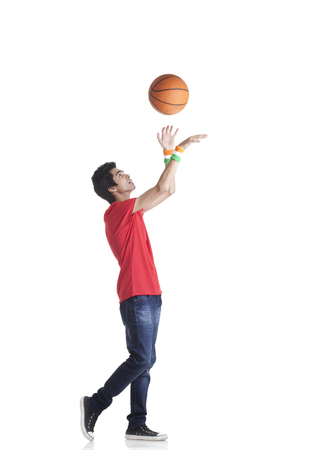 Side view of young boy in casuals tossing basketball over white background
