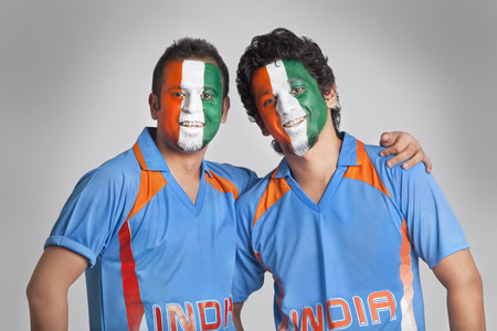 Male cricket fans with face painted in tricolor standing together over colored background Stock Photo