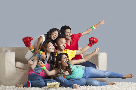 Excited young friends watching boxing match together at home