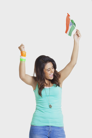 Excited young woman cheering with clenched fists while holding Indian flag over white background Stock Photo
