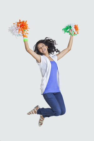 Full length of young woman jumping in mid-air with Indian tricolor pom-poms over colored background
