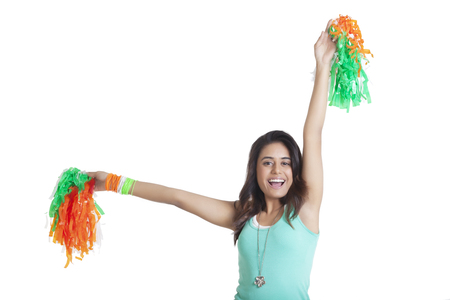 Portrait of young woman holding out tricolor pom poms over white background