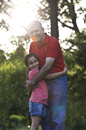 granddad: Portrait of grandfather and granddaughter hugging in a park Stock Photo