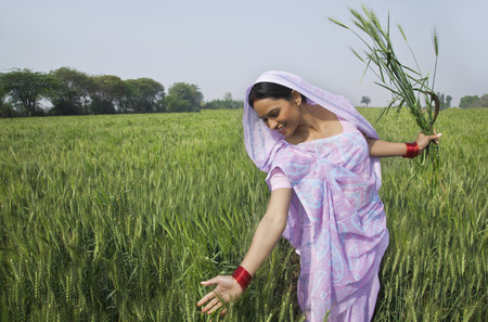 Happy Indian female farm worker gliding through wheat field Stock Photo