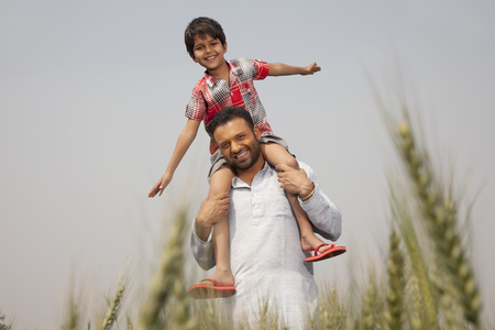 Portrait of a man carrying little boy on shoulders Stock Photo